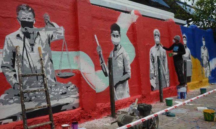 माहिम रेल्वे स्थानकाच्या भिंतीवर कोरोना योद्ध्यांचे चित्र काढताना एक कलाकार